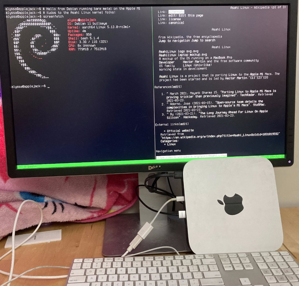 """Photograph of a Mac Mini against a monitor displaying a shell prompt, the Debian spiral, and the Wikipedia page """"Asahi Linux"""" in the text-based browser """"links""""."""